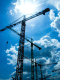 Cranes Construction Site. On blue sky and clouds background Royalty Free Stock Photo