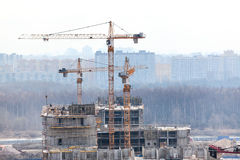 Cranes on construction site build high-rise building Royalty Free Stock Image
