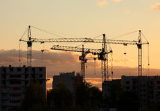 Cranes on construction site house at sunset Royalty Free Stock Photos