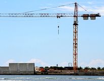 Cranes in construction site by the sea for the construction of a Royalty Free Stock Photos