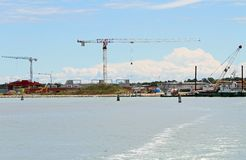 Cranes in construction site by the sea for the construction of a Stock Images
