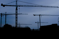 Cranes at construction site. Cranes on construction site silhouetted against blue sky stock photo