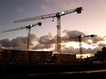 cranes on a construction site at sunset royalty free stock photography
