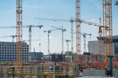 Cranes and construction workers onconstruction site Stock Photo