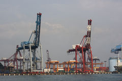 Cranes at the Docks. This is Keelung Port. It's one of the busiest ports in East Asia. Here they are moving a container loaded with cargo stock images