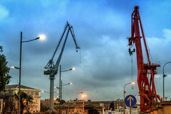 Cranes in the evening sky. View of the port in the evening, the occurrence of high crane operates powerfully and persuasively Royalty Free Stock Photo