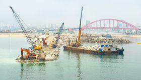 Cranes and excavator machines in a pier construction site Stock Images