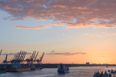 Cranes in a harbor at sunset Royalty Free Stock Photos
