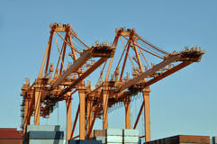 Cranes in a harbour. Two heavy cranes with lots of containers in a harbour royalty free stock photography