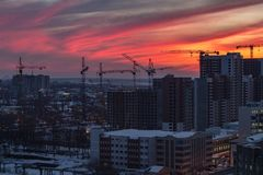 High-rise buildings construction site on crimson sunset sky background. Voronezh, Russia stock image