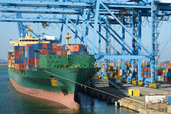 Cranes load containers on   large transport ship Stock Image
