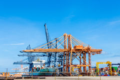 Cranes load containers on a large transport ship Stock Image