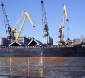 Cranes loading ship. With coal Stock Photo