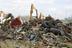 Cranes Moving Waste at the Scrap Yard. Cranes fitted with a grappling hook or claw moves metal and trash at the recycling yard Stock Photos