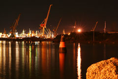 Cranes in night harbour. With reflection on the sea Royalty Free Stock Photo