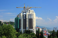 Cranes over high rise building. Industrial cranes over high rise building under construction, Sochi, Russian Federation Stock Photo
