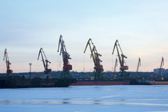 Cranes in the port, shipyard. in the evening, at sunset. stock photo