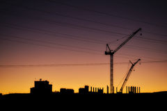 Cranes, Power Lines and Industrial Factories Silhouetted Against the Sunset Royalty Free Stock Image