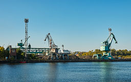 Cranes on the quay of the river. Under blue sky Royalty Free Stock Photo