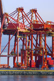 Cranes in red at an industrial port. With a bridge in the back Royalty Free Stock Photography