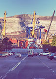 Cranes are. Road rests on the seaport where there is a cargo ship unloading stock image