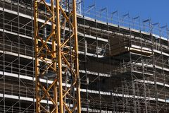 Cranes and scaffolding during construction of a building on a site Stock Photography