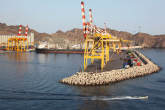 Cranes in shipping port near mountains Royalty Free Stock Image