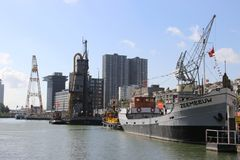 Cranes, ships and lighthouse at the maritime museum in Rotterdam on the public street in the Netherlands. Cranes, ships and lighthouse at the maritime museum in stock photography