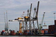 Cranes and ships in the port of Rotterdam at Heijpaat in the waalhaven harbor, The Netherlands. stock image