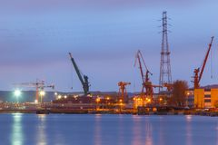 Cranes on shore in Gdansk shipyard at night. Gdansk, Poland- March 24, 2014: Cranes on shore in Gdansk shipyard at night Stock Photos