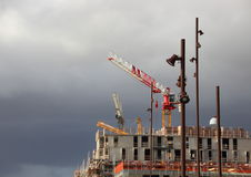 Cranes and Street Lamps at Building Site with Dark Clouds Royalty Free Stock Photos