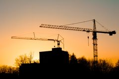 Cranes in the sun. Sunset behind buildings and cranes in Freiburg, Germany Stock Images