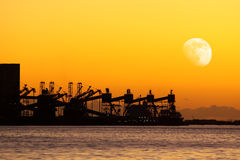 Cranes at Sunset. Sunset with silhouettes of cranes in a cereal cargo port Stock Image