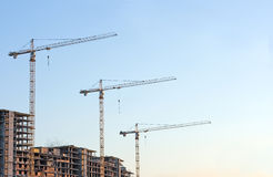 Cranes at sunset on construction site Stock Image