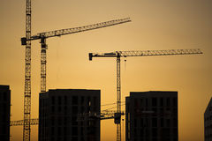 Cranes at sunset. Industrial construction cranes and building silhouettes over sun at sunrise. Stock Images