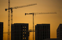 Cranes at sunset. Industrial construction cranes and building silhouettes over sun at sunrise. Royalty Free Stock Images