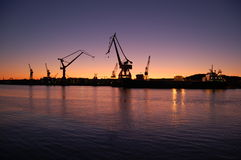 Cranes at sunset near harbour Royalty Free Stock Photography