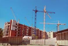 Cranes under a blue sky. Many tall buildings under construction and cranes under a blue sky Stock Photo