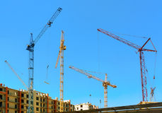 Cranes under a blue sky. Many tall buildings under construction and cranes under a blue sky Stock Photography