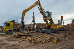 Cranes at warehouse territory logs are unloaded from the truck. Royalty Free Stock Image