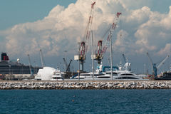 Cranes at Work in Boatyard near Lighthouse Royalty Free Stock Photos