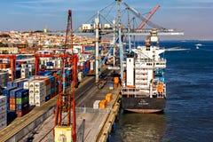 Cranes working at a cargo ship. Lisbon shipyard, Portugal Royalty Free Stock Photo