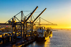 Cranes working at a cargo ships. Lisbon shipyard, Portugal Royalty Free Stock Images