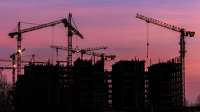 Cranes working on construction of the housing estate in former Royalty Free Stock Images