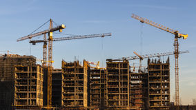 Cranes working on construction of the housing estate in former Royalty Free Stock Photo