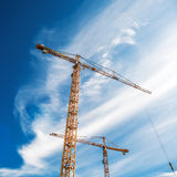 Cranes Working on Construction Site. Against Blue Sky, Square Format Royalty Free Stock Photos