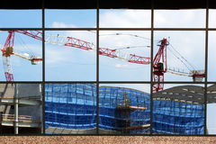 Cranes and yard reflected in glass window Royalty Free Stock Photo