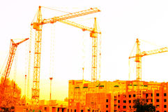 Cranes with a yellow tinge on the construction of a new house Stock Photo