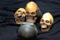 Crani umani e teste di legno nere pesanti su fondo nero stile e allenamento di natura morta di concetto Fotografia Stock Libera da Diritti