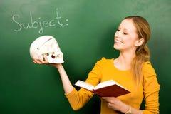 Cranio e libro della holding della ragazza Fotografia Stock Libera da Diritti